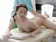 Pigtailed dark haired  Izi lies on the massage table as his strong mitts caress grease into her legs, back, and ass. His thumbs and tongue find her pussy, titillating the  to wetness. He meets her dream by slipping his cock into her from behind, fucking his stellar client deep in her  hole. Sensual kissing and more positions fill the scene until he finishes off hard.